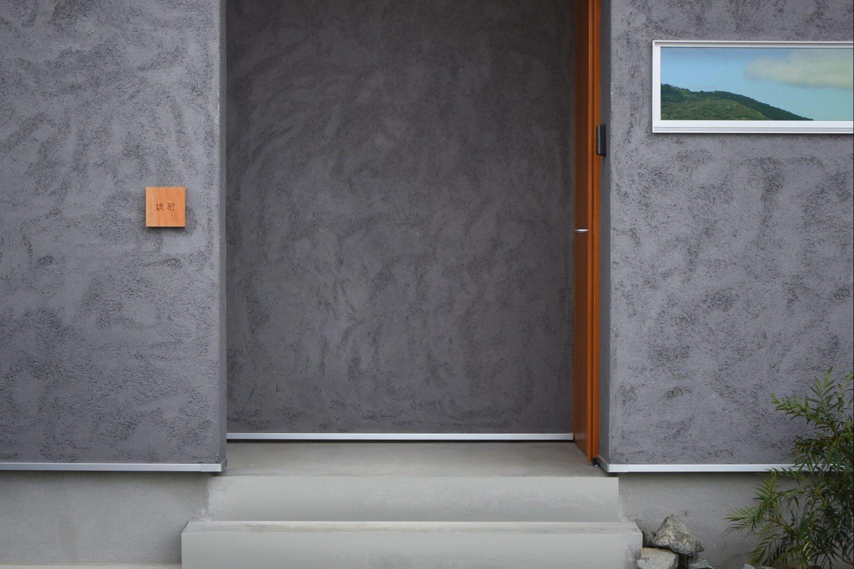 滴水(たるみず)の住宅:グレーのシラス壁は特徴的な仕上方です。木製の玄関ドアと杉の軒天がとても合います。