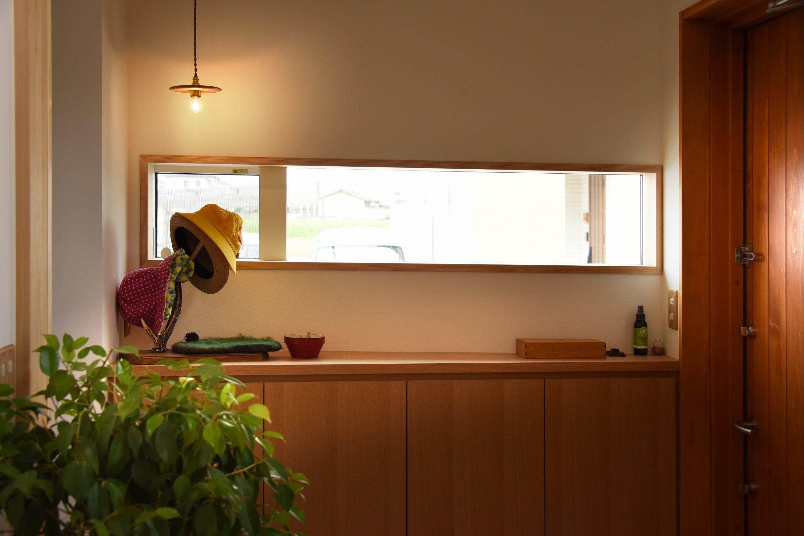 滴水(たるみず)の住宅:明るい玄関。檜の木製のドアとタモの突板の玄関収納、窓枠も無垢材を使い、子供たちが帰ってきてホッとできるような場所になっています。