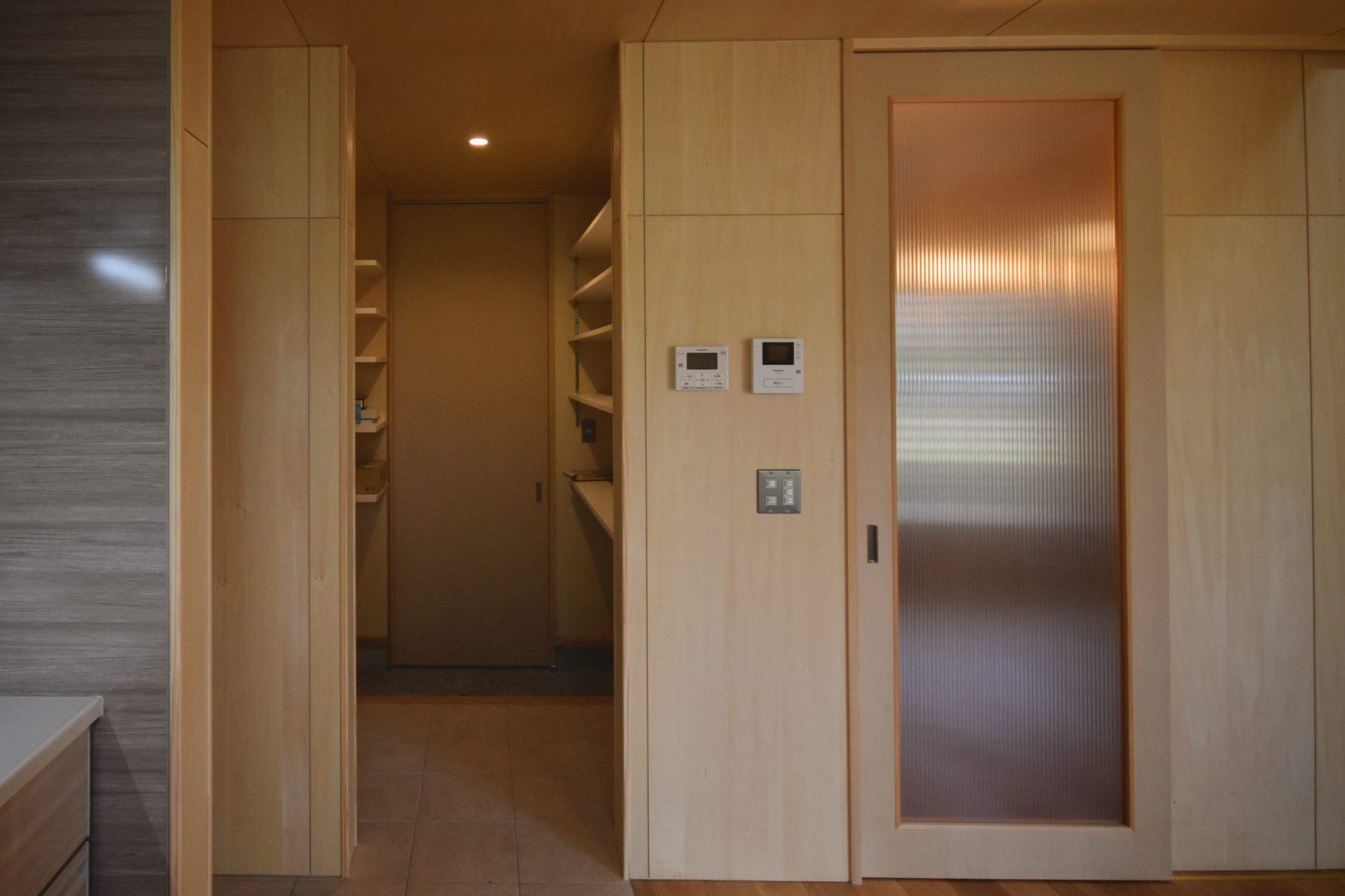 田迎の住宅:扉の奥は玄関~土足でも入れるパントリー~キッチンと一直線に動線をとっています。