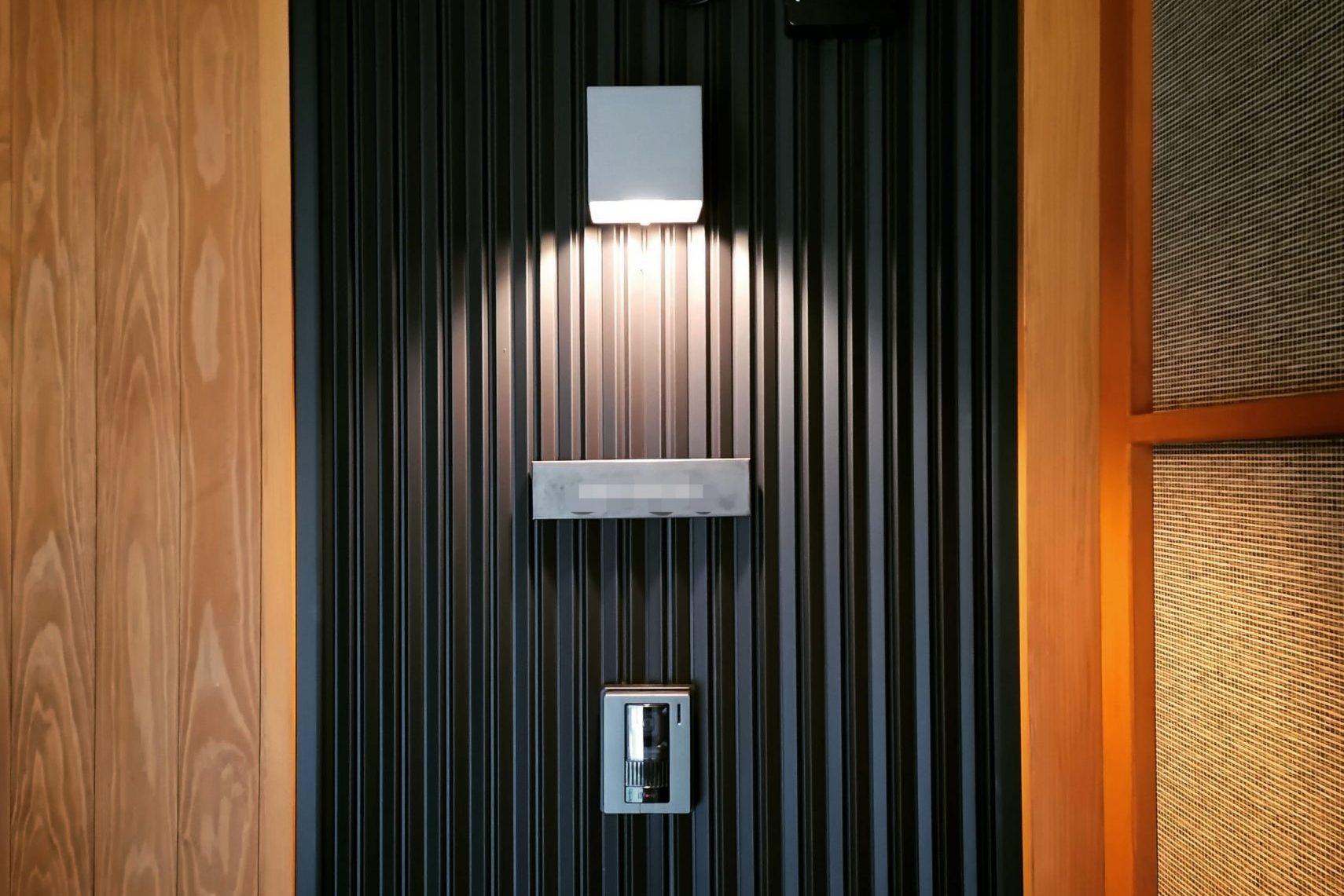 田迎の住宅:黒いガルバリウムの壁に、スッキリした玄関灯、木製の木肌の見える造作建具の色のコントラストが印象的です。